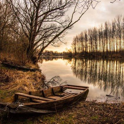 Osamocená loďka na osmoceném místě. Nacházíme se v řídkém, avšak ponurém lese.